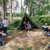 dzieci odpoczywają w lesie w szałasach